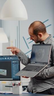 Mężczyzna kierownik projektu trzymający laptopa i wskazujący na wyświetlacz pokazujący kobietę inżyniera przemysłowego, która pracuje na komputerze nad rozwojem prototypu nowej maszyny