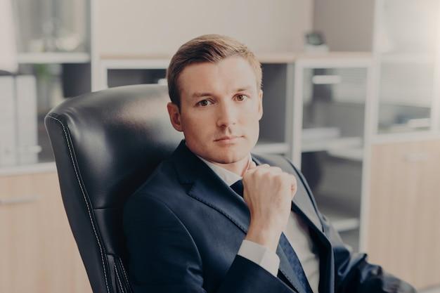 Mężczyzna kierownik siedzi na krześle w swoim gabinecie