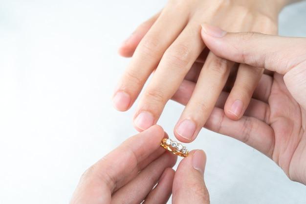 Mężczyzna kładąc pierścionek z brylantem na ręce kobiety na białym tle