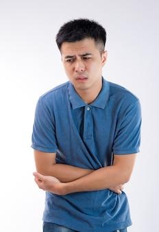 Mężczyzna kładąc ręce na brzuchu pojęcie bólu brzucha na białym tle