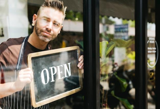Mężczyzna kładzenie na sklepu otwartym znaku