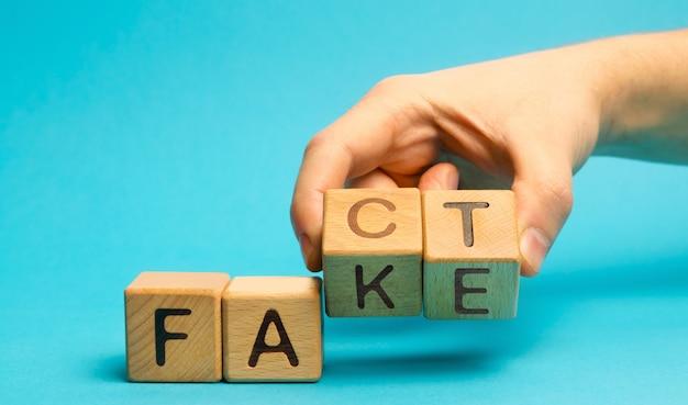 Mężczyzna kładzie drewniane klocki słowami fakt i podróbka. pojęcie wiadomości i fałszywych informacji.