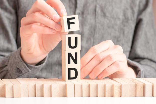Mężczyzna kładzie drewniane kostki z literą f ze słowa fund.