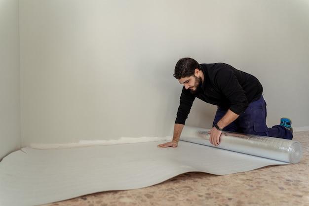 Mężczyzna kładzie izolację na ziemi, aby położyć drewniany laminat na ziemi