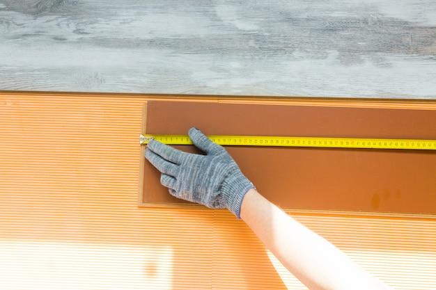 Mężczyzna kładzie nową podłogę laminowaną. naprawa w mieszkaniu. pracownik naprawia podłogę. proces układania laminatu