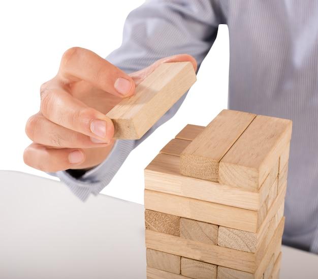 Mężczyzna kładzie ostatni drewniany klocek układanki