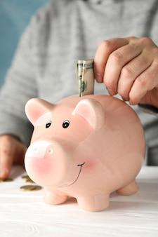 Mężczyzna kładzie pieniądze w skarbonka na białym drewnianym stole