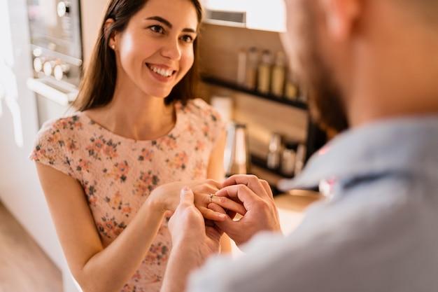 Mężczyzna kładzie pierścień na palcu swojej dziewczyny