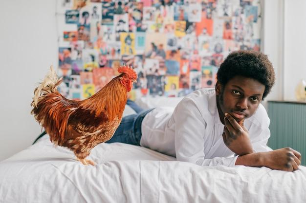 Mężczyzna kłama na białym łóżku z kurczakiem