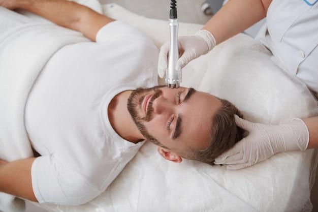 Mężczyzna klient otrzymuje zabieg rf-lifting twarzy w klinice kosmetologii
