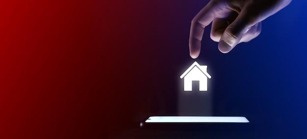 Mężczyzna kliknie palcem ikonę otwartego domu. symbol domu dla projektu witryny sieci web, interfejs użytkownika. to wirtualna projekcja z telefonu komórkowego. neony, czerwono-niebieskie światła.