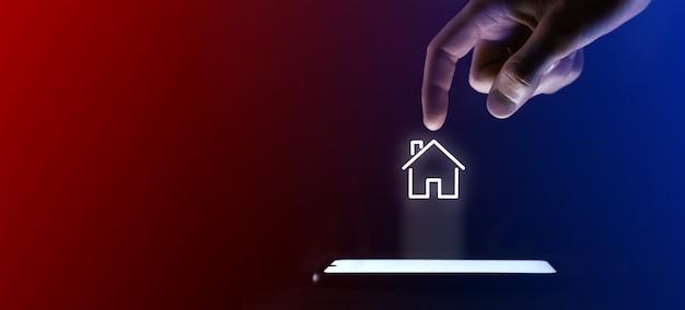 Mężczyzna kliknie palcem symbol otwartego domu. symbol domu dla projektu witryny internetowej, logo, aplikacji, interfejsu użytkownika. to wirtualna projekcja z telefonu komórkowego. neony, czerwono-niebieskie światła.