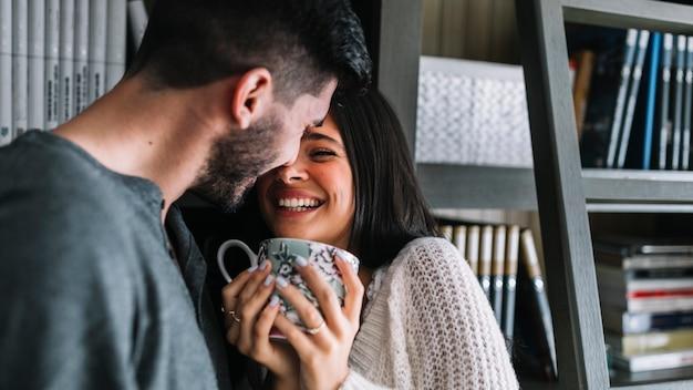 Mężczyzna kochający jej uśmiechniętej kobiety trzyma filiżankę