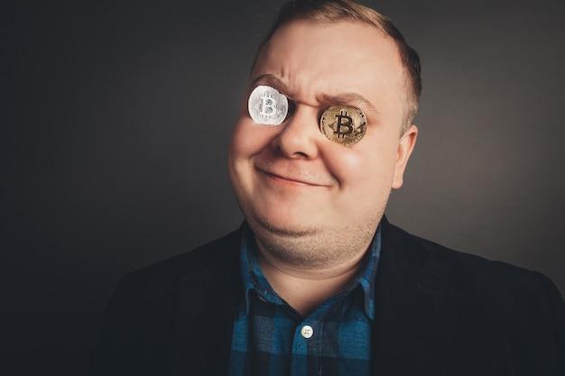 Mężczyzna kochanek bitcoin ze złotą monetą na oczach