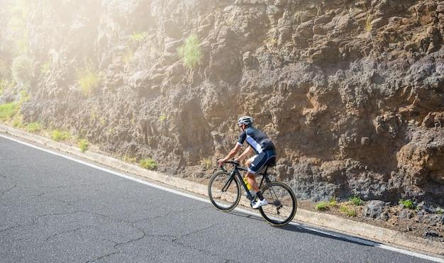 Mężczyzna kolarz szosowy, atakujący podjazd na teneryfie, hiszpania