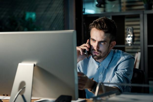 Mężczyzna komunikuje się przez telefon opóźnionego w biurze