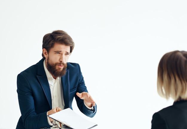 Mężczyzna komunikuje się z kobietą i kolegami w pracy zespołu biurowego w jasnym tle