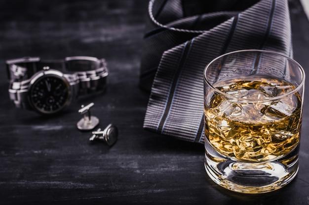 Mężczyzna koncepcja na dzień ojca. krawat, zegarki, spinki do mankietów i kieliszek whisky z lodem