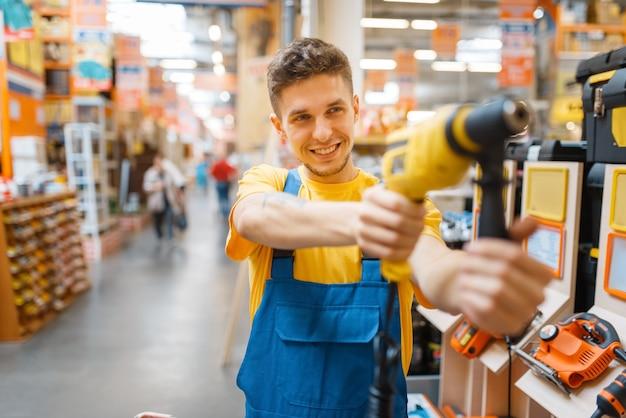 Mężczyzna konstruktor wybiera elektryczny śrubokręt w sklepie z narzędziami. konstruktor w mundurze obejrzyj towary w sklepie dla majsterkowiczów