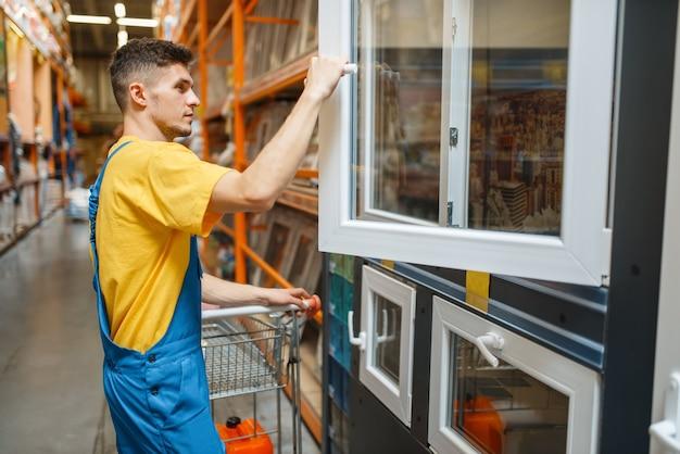 Mężczyzna konstruktor wybiera okna w sklepie z narzędziami. konstruktor w mundurze obejrzyj towary w sklepie dla majsterkowiczów