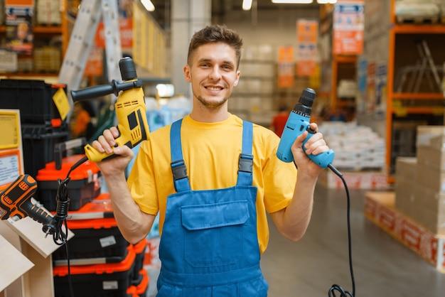 Mężczyzna konstruktor z elektronarzędziami w sklepie z narzędziami. konstruktor w mundurze obejrzyj towary w sklepie dla majsterkowiczów