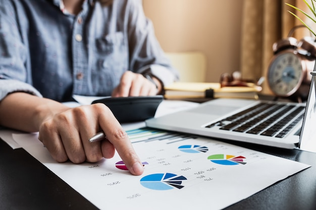 Mężczyzna konsultant inwestycyjny analizujący roczne sprawozdanie finansowe firmy zestawienie bilansowe pracujące z wykresami dokumentów.