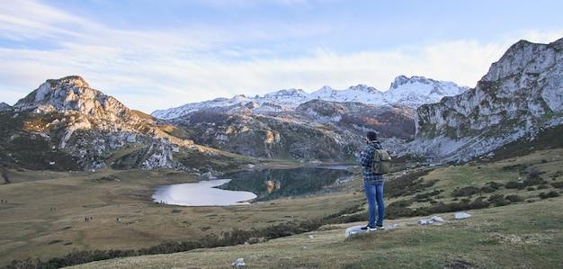 Mężczyzna kontempluje jezioro ercina z zaśnieżonymi górami w asturii (hiszpania)