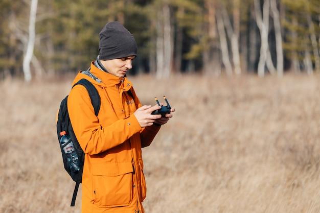 Mężczyzna kontroluje dron quadcopter jesienią na zewnątrz.