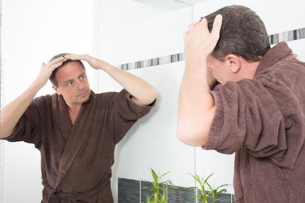 Mężczyzna kontroluje wypadanie włosów w łazience, patrząc w lustro i naprawiając włosy