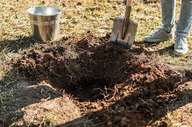 Mężczyzna kopie dziurę łopatą, aby zasadzić drzewo