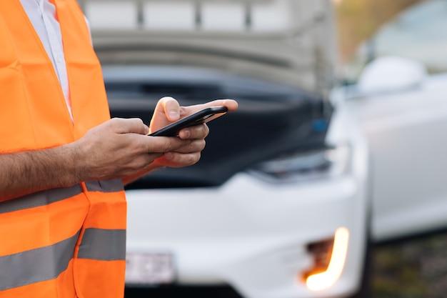 Mężczyzna korzysta z telefonu po awarii samochodu elektrycznego