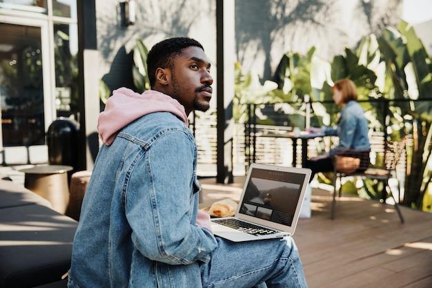 Mężczyzna korzystający z laptopa w kawiarni