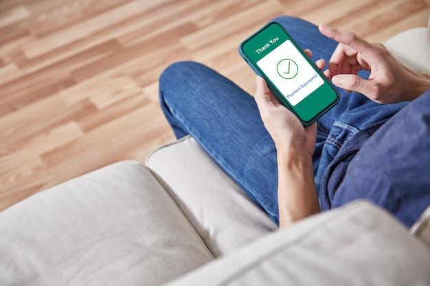 Mężczyzna korzystający z płatności online smartfonem w domu
