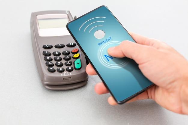 Mężczyzna korzystający z technologii nfc na smartfonie, aby zapłacić rachunek