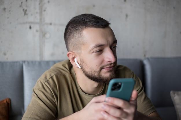 Mężczyzna korzystający z telefonu komórkowego i cieszący się piosenkami w bezprzewodowych słuchawkach w kawiarni