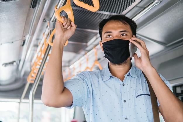 Mężczyzna korzystający z telefonu komórkowego, stojąc w transporcie publicznym, nosi maskę