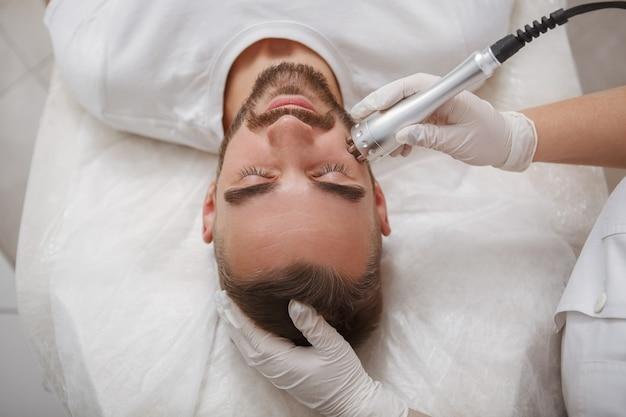 Mężczyzna korzystający z zabiegu kosmetologii rf liftingu twarzy przez profesjonalną kosmetyczkę