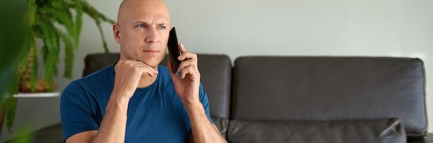 Mężczyzna korzystający ze smartfona w domu, siedzący na kanapie w domu