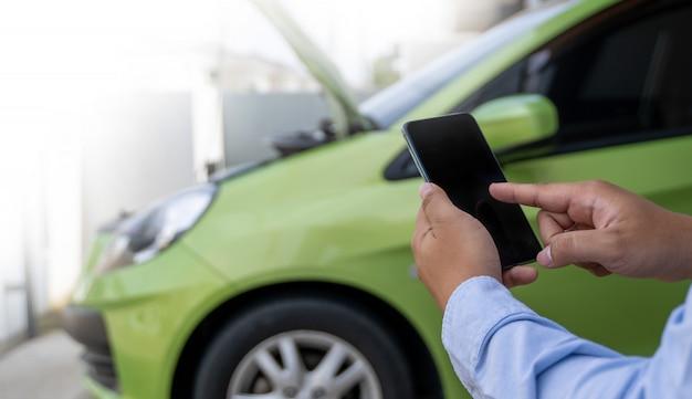 Mężczyzna korzystanie z telefonu komórkowego w celu pomocy pomoc w zepsutym samochodzie pomaga zatrzymać awarię samochodu