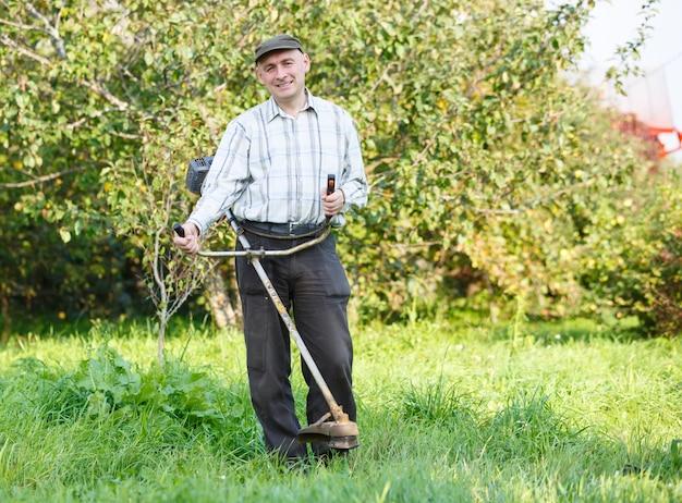Mężczyzna kosi trawę w ogrodzie