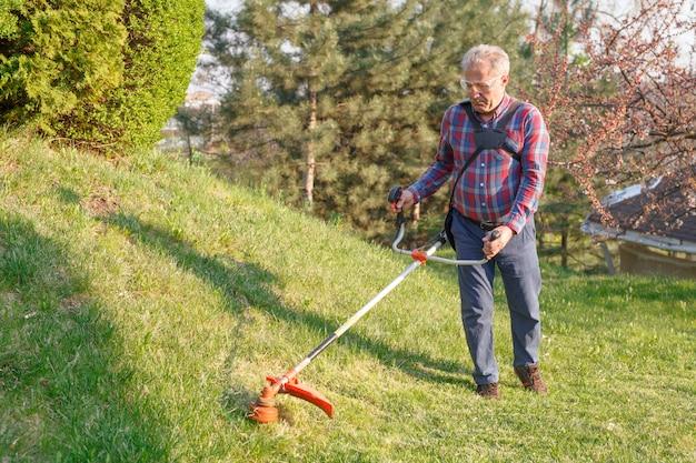 Mężczyzna kosi trawnik za pomocą kosiarki.