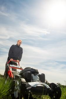 Mężczyzna koszący, koszący trawę na swoim ogromnym podwórku, zielone pole przez silnikową kosiarkę ogrodową, koncepcja ogrodnictwa