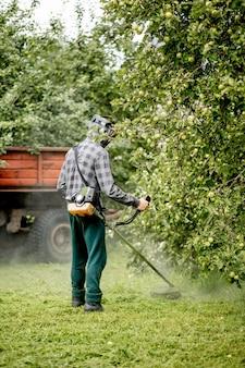 Mężczyzna koszący trawnik w swoim ogrodzie. ogrodnik koszący trawę. styl życia.