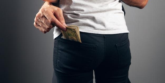 Mężczyzna kradnie pieniądze z tylnej kieszeni kobiety