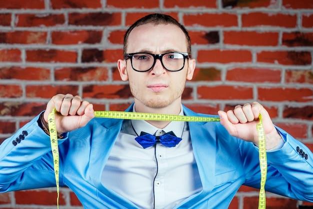 Mężczyzna krawcowa krawcowa w stylowym garniturze i okularach trzyma miarkę. koncepcja tworzenia markowych ubrań dla mężczyzn