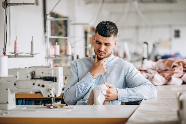 Mężczyzna krawiec pracuje w szwalnej fabryce