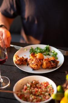 Mężczyzna kroi mięso nożemmężczyzna je mięsogrilowane mięso wołowe jedzenie kebab sałatka mięso z ziołami