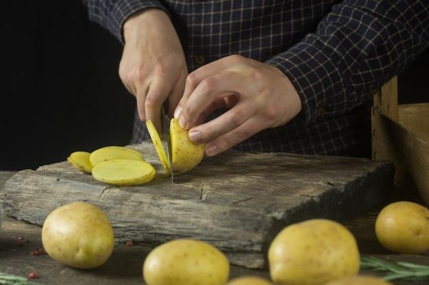 Mężczyzna kroi ziemniaki w kuchni na rustykalnym drewnianym stole
