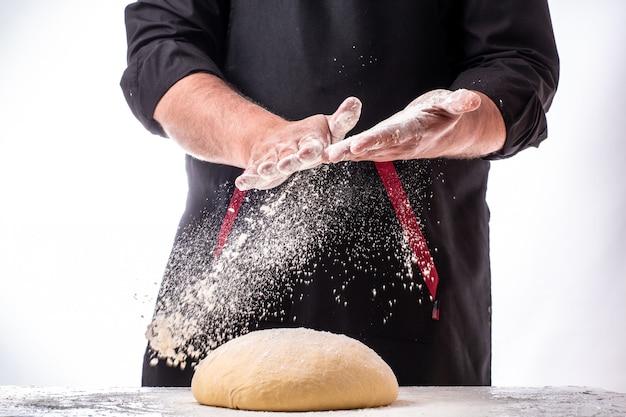 Mężczyzna kropi mąkę nad świeżym ciastem na kuchennym stole. ciasto na białym stole pokrytym proszkiem