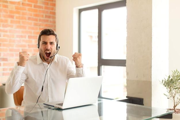 Mężczyzna krzyczy agresywnie ze złością lub z zaciśniętymi pięściami świętując sukces
